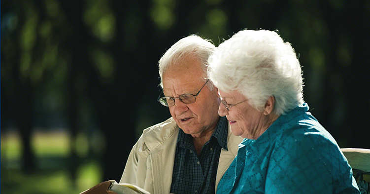 Elderly couple looking at a book